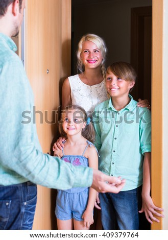 Hospitable man greeting smiling guests at apartment entrance