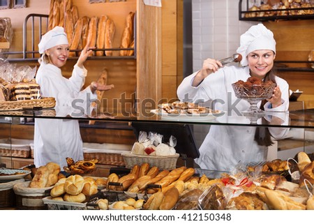Hospitable women with delicious the cream pies at the bakery display. Focus on young women  - stock photo