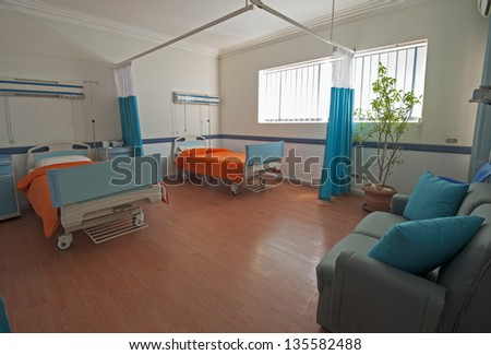 Hospital beds in a private hospital ward ward with plant and sofa - stock photo