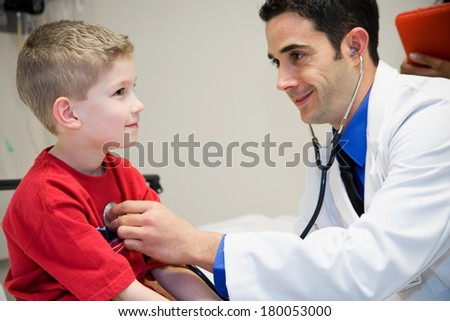 Hospital: Boy Sits Still So Doctor Can Check Heart - stock photo