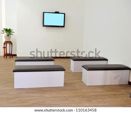 Hospital or clinic waiting room with stools and flat screen TV. - stock photo
