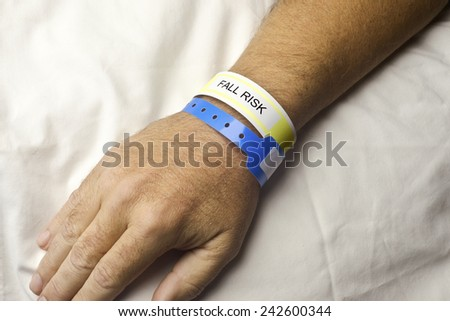 Hospital patient with fall risk bracelet on wrist. - stock photo