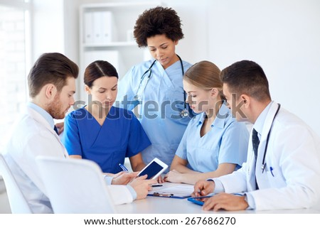 hospital, profession, people and medicine concept - group of doctors with tablet pc computers meeting at medical office - stock photo