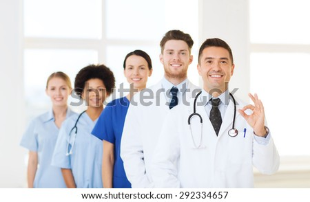 hospital, profession, people and medicine concept - group of happy doctors at hospital showing ok hand sign