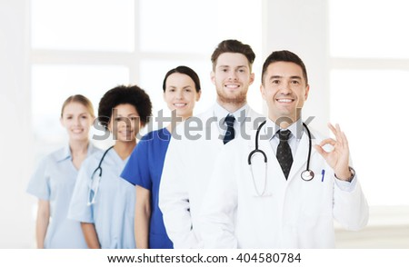 hospital, profession, people and medicine concept - group of happy doctors at hospital showing ok hand sign - stock photo
