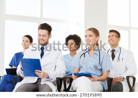 hospital, profession, people and medicine concept - group of happy doctors on seminar in lecture hall at hospital - stock photo