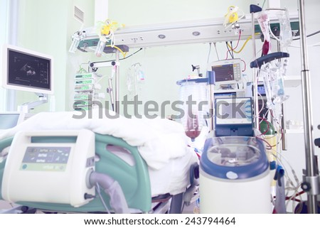 hospital room in intensive care unit occupied by seriously ill patients and filled with modern diagnostic and therapeutic equipment - stock photo