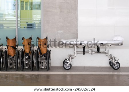 Hospital wheel chairs lined up with bed - stock photo