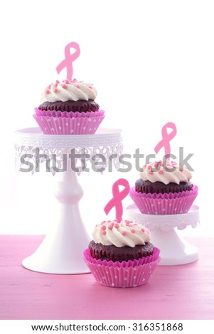 Host an Event for Pink Ribbon Day charity for womens breast cancer awareness with pink and red velvet cupcakes, with coffee and tea. - stock photo