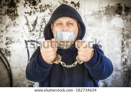 Hostage in handcuffs with tape on the mouth - stock photo