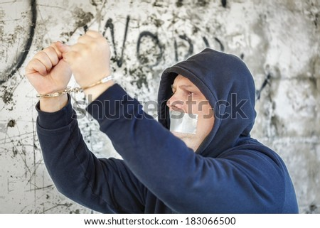 Hostage in handcuffs with tape on the mouth near wall - stock photo