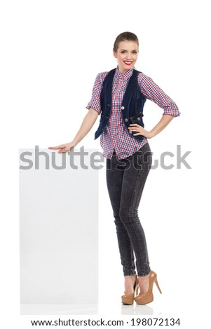 Hostess is standing close to blank placard. Full length studio shot isolated on white. - stock photo