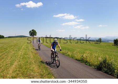 HOSTYN HILLS, CZECH REPUBLIC - JULY 4, 2015. Two unidentified bikers go on their bikes on the new open bike paths in Hostyn hills, Czech republic. - stock photo