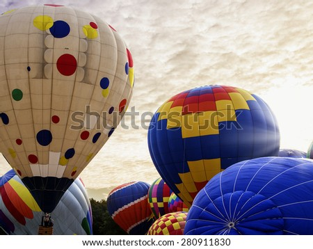 Hot air ballons taking off and airing up at sunrise during a festival