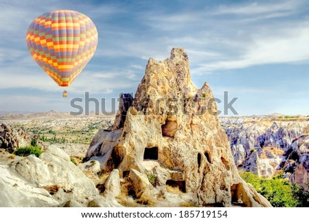 Hot air balloon above a the gorgeous landscape of Cappadocia , Turkey  - stock photo