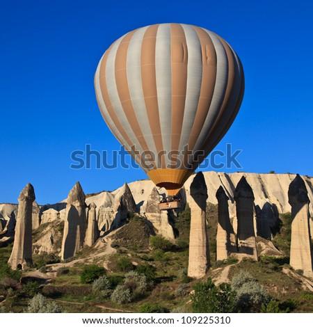 Hot air balloon drifting over fairy chimneys in Cappadocia, Turkey - stock photo