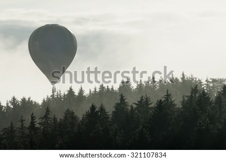 Hot air balloon floating over the misty autumnal forest - stock photo