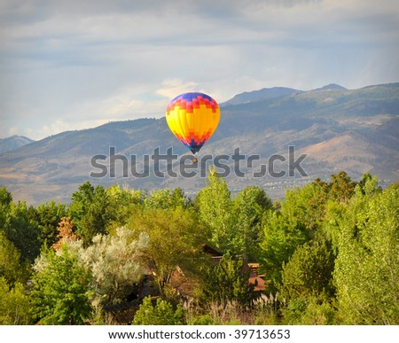 Hot Air Balloon floating over trees - stock photo