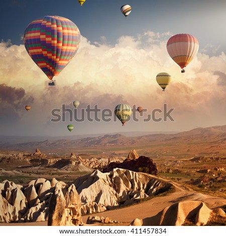 Hot air balloon flying above rocky landscape in Cappadocia, Turkey - stock photo
