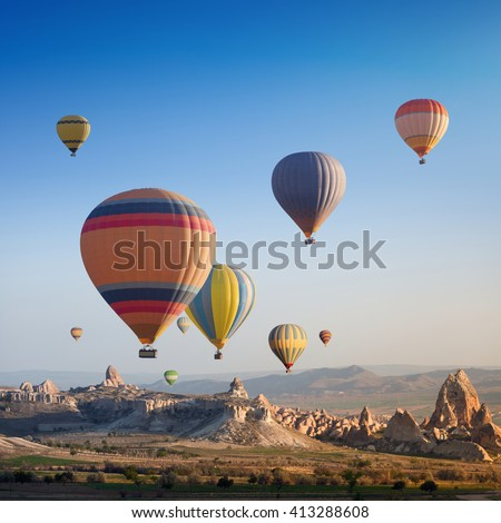 Hot air balloon flying above rocky landscape in Cappadocia, Turkey