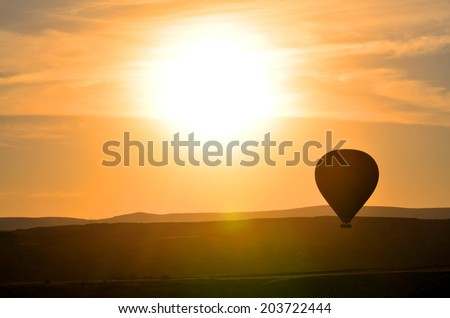 Hot air balloon flying at orange sunset sky Cappadocia Turkey - stock photo