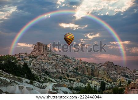 Hot air balloon flying over Cappadocia with rainbow - stock photo