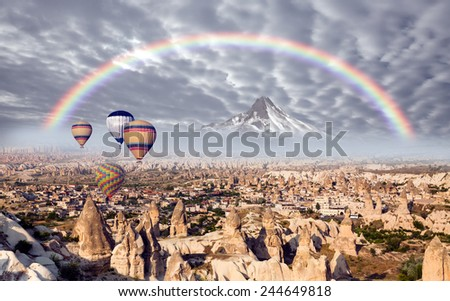 Hot air balloon flying over Cappadocia with rainbow - stock photo