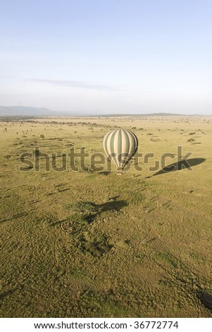 Hot air balloon flying over Serengeti National Park, Tanzania - stock photo