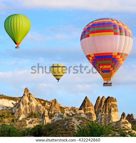 Hot air balloon flying over spectacular landscape of fairy chimneys carved in volcanic tuff by erosion. Cappadocia, Turkey - stock photo