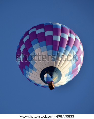 Hot air balloon flying overhead against blue sky
