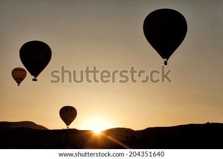 Hot air balloon flying taking off at sunrise over landscape at Cappadocia Turkey  - stock photo