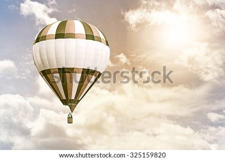 hot air balloon flying through a cloudy sky against the sun - stock photo