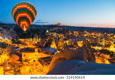 Hot Air Balloon flying town night Goreme landscape Cappadocia Turkey - stock photo