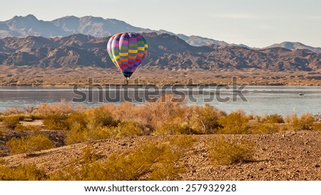 Hot air balloon hovers over the still waters of Lake Havasu.  The beautiful Chemehuevi Mountains are shown in the background on the California side of Lake Havasu