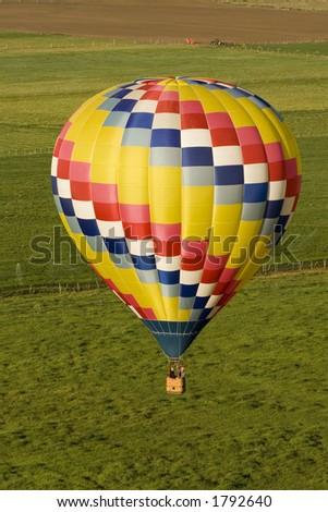 Hot Air Balloon in Flight over Fields - stock photo
