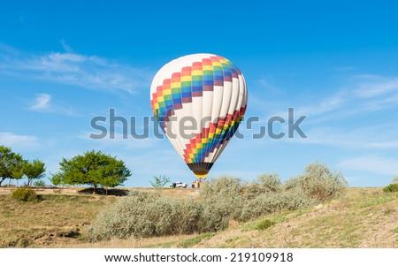Hot air balloon landing on Cappadocia, Turkey - stock photo