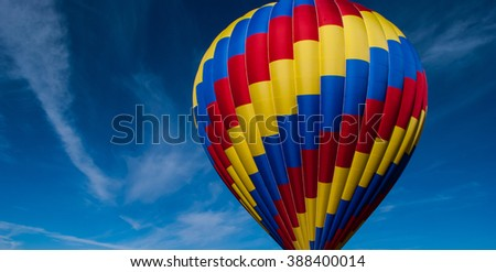 hot air balloon lifting off in the rocky mountain of Colorado with a nice blue sky background with a colorful yellow blue and red balloon  - stock photo