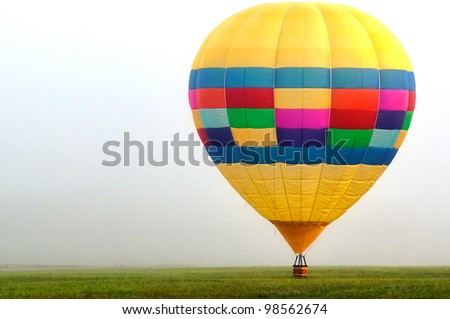 Hot air balloon on the ground on a foggy morning