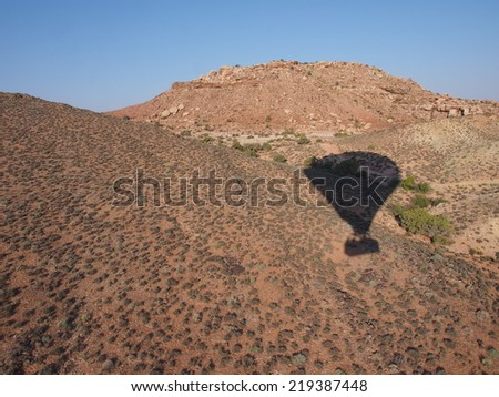 Hot Air Balloon Over Desert Hills - stock photo