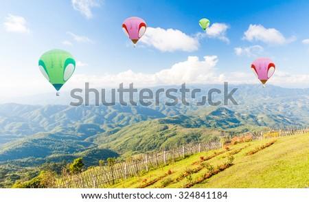 Hot air balloon over fields against blue sky - stock photo