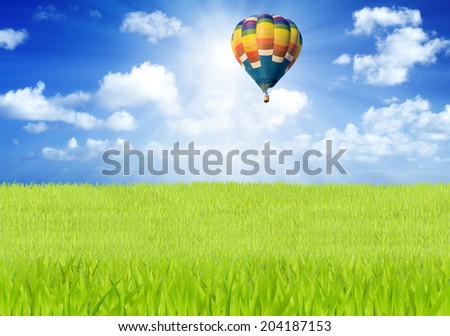 Hot air balloon over green fields and blue sky background
