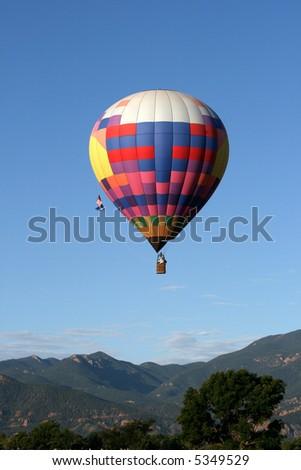 Hot air balloon over mountains - stock photo