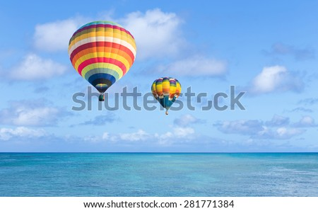Hot air balloon over ocean and clouds blue sky - stock photo