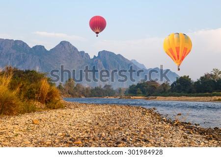 Hot air balloon over river in Vangvieng, Laos - stock photo