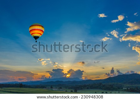 Hot air balloon over the fields at sunset - stock photo