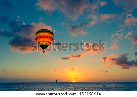 Hot air balloon over the sea at sunset - stock photo