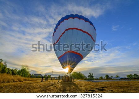 Hot air balloon preparing for launch with sunburst