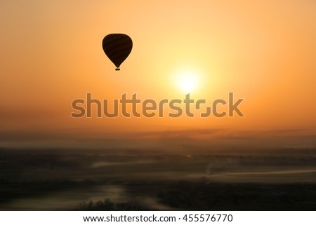 Hot air balloon silhouetted in the  early morning sun during  flight, with foggy patches in the Valley of the Kings, Egypt, Africa - stock photo