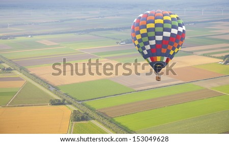 Hot air balloon with green Dutch landscape from above - stock photo
