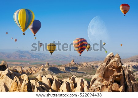 Hot air ballooning is most popular attraction in Kapadokya. Big moon in clear blue sky. Hand carved rooms in limestone rocks near Goreme, Cappadocia, Turkey. Elements of this image furnished by NASA.